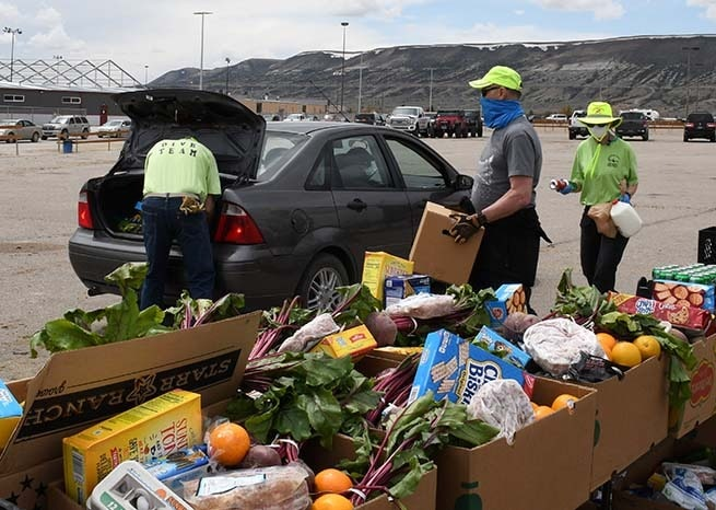 Volunteers loading food boxes into cars at distribution event